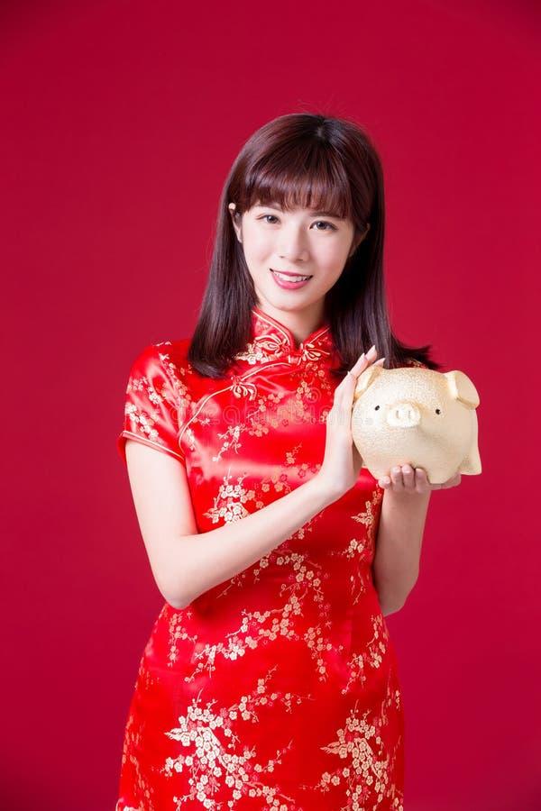 Banca del maiale di manifestazione della donna di Cheongsam fotografie stock