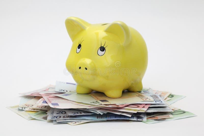 Banca Piggy che si leva in piedi in cima alle euro banconote fotografia stock