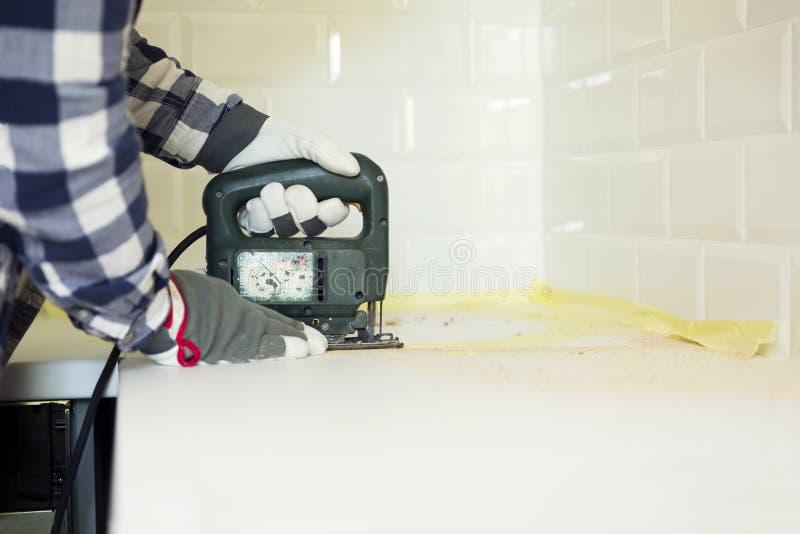 Bancada da cozinha do corte do homem usando a serra de vaivém elétrica Impro home imagem de stock royalty free
