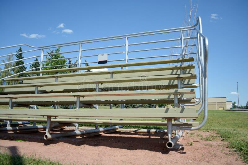 Bancada no campo do basefield em um parque de comunidade local imagem de stock
