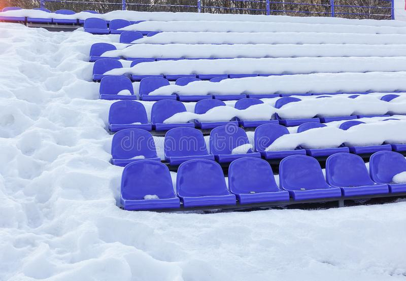 Bancada no inverno, cadeiras dos fãs - lugares vazios do estádio dos esportes dos anfiteatros cobertos pela neve imagens de stock