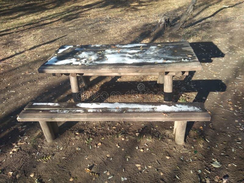 banch de madeira e tabela cobertos em parte pela neve imagens de stock royalty free
