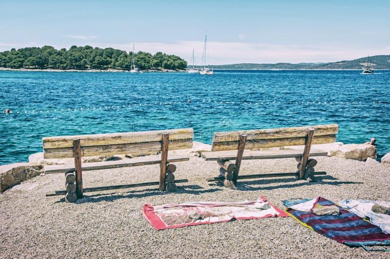 Banchi di legno ed asciugamani sulla spiaggia, filtro blu immagine stock libera da diritti