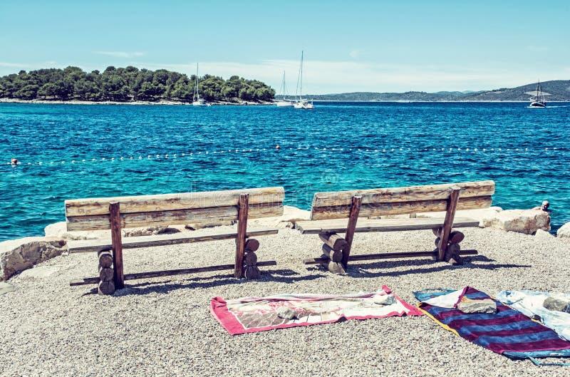 Banchi di legno ed asciugamani sulla spiaggia, filtro blu immagine stock