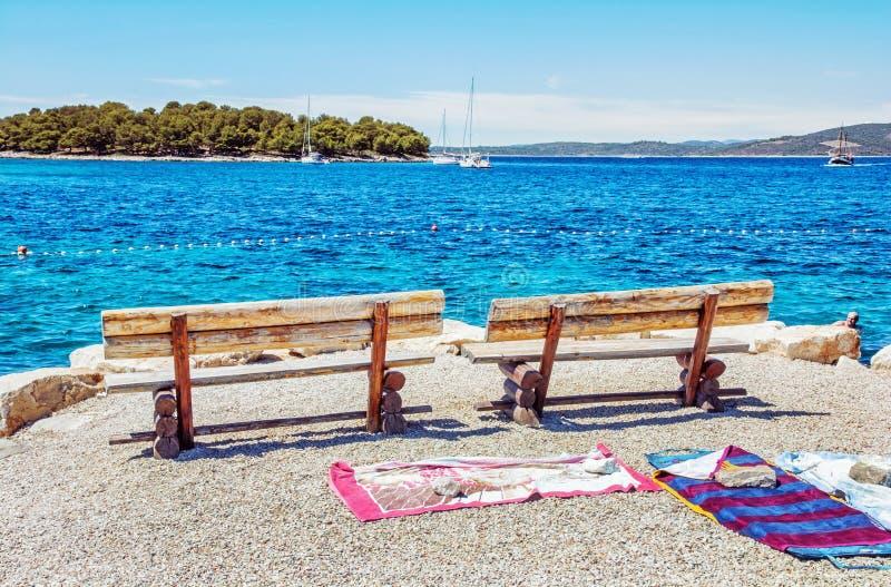 Banchi di legno ed asciugamani sulla spiaggia, Solta fotografia stock libera da diritti