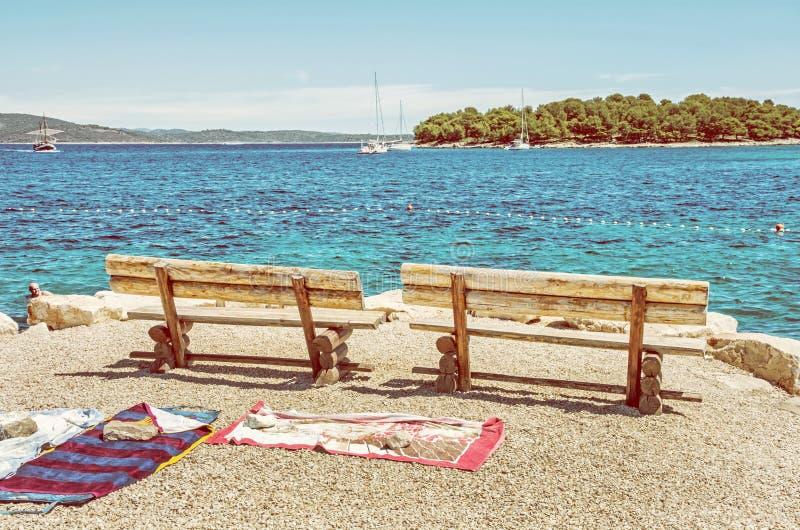 Banchi di legno ed asciugamani sulla spiaggia, Solta, filtro giallo immagini stock