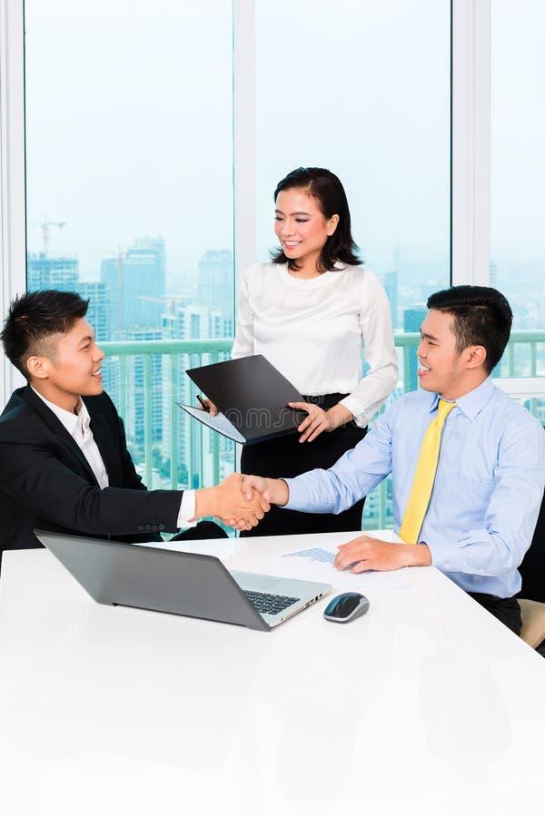 Banchiere asiatico che consiglia uomo in ufficio fotografia stock