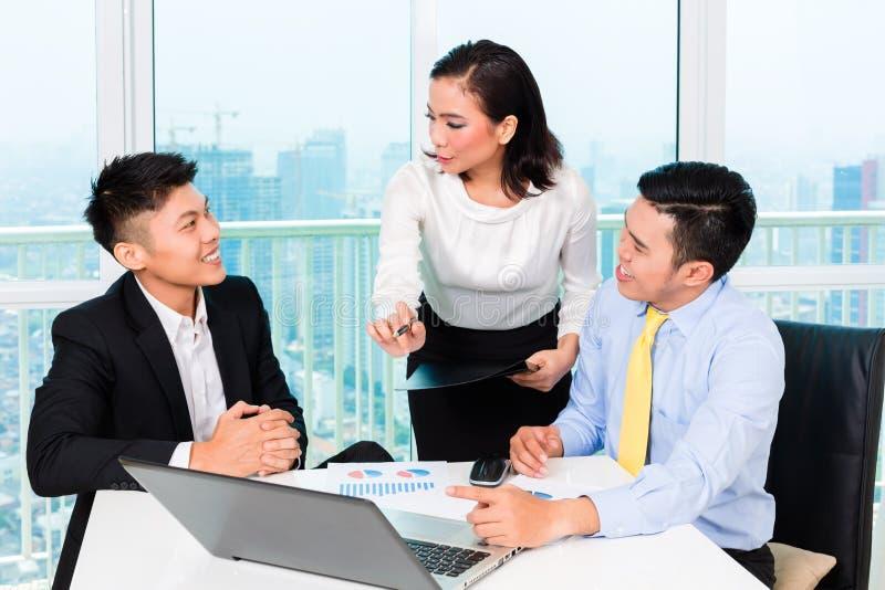Banchiere asiatico che consiglia uomo in ufficio fotografie stock