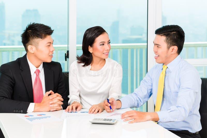 Banchiere asiatico che vende assicurazione alle coppie fotografia stock