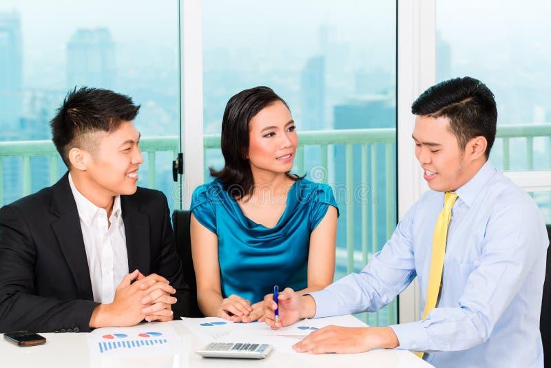 Banchiere asiatico che vende assicurazione alle coppie fotografia stock libera da diritti