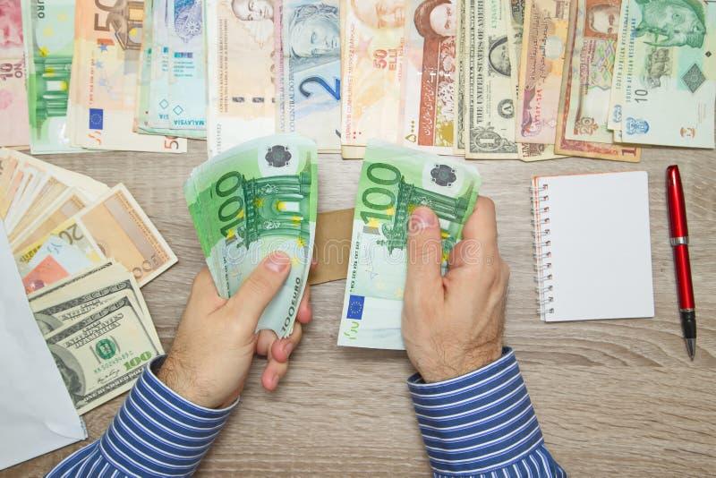 Banchiere che conta gli euro alla sua tavola dell'ufficio, immagine stock