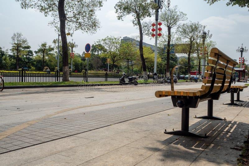 Banco amarelo vazio sob a árvore no pedestre ao lado da rua no Midtown foto de stock royalty free