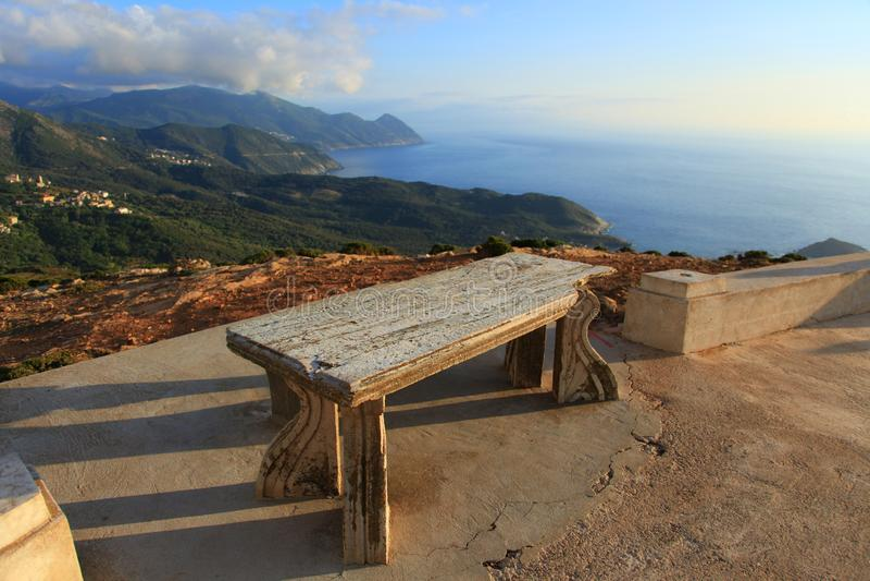 Banco antico della pietra sui precedenti delle montagne, delle nuvole e del paesaggio verdi del mare immagine stock