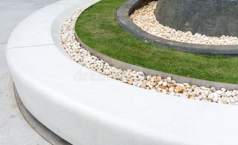 Banco blanco de la piedra de la curva adornado con la grava y el césped blancos FO foto de archivo