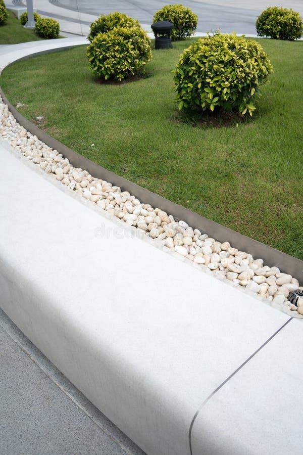 Banco blanco de la piedra de la curva adornado con la grava y el césped blancos FO fotografía de archivo libre de regalías