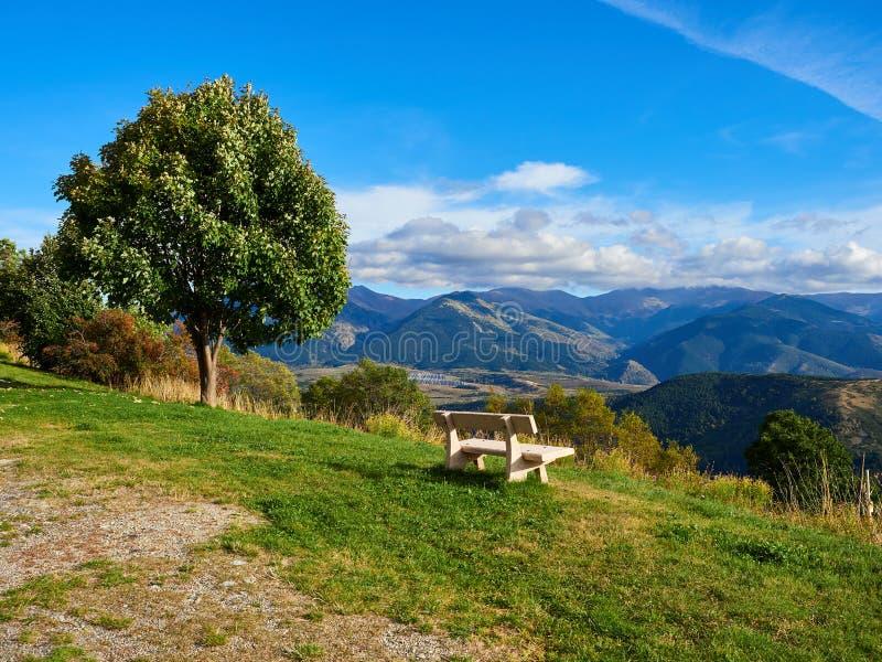 Banco blanco que se sienta en la cima de una montaña en el lado de un árbol, Font Romeu de la roca del granito fotos de archivo