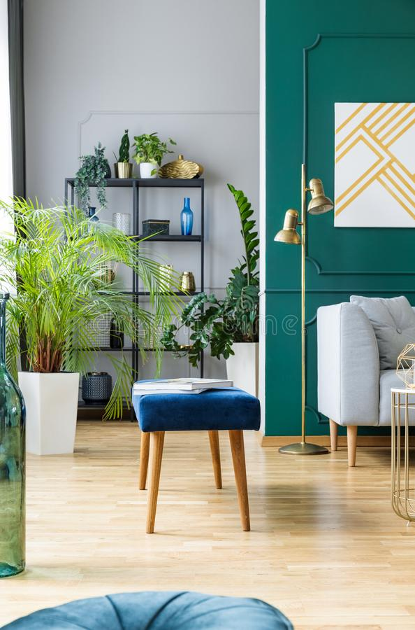 Banco blu accanto al sofà grigio nell'interno ispirato tropicale con i colori dell'oro e di verde immagini stock libere da diritti