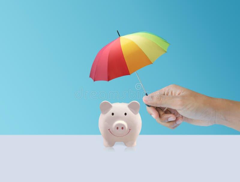 Banco cerâmico leitão do rosa com o guarda-chuva colorido do arco-íris, seguro imagem de stock