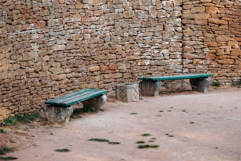 Banco cerca de la pared antigua pavimentada con los ladrillos en parque fotografía de archivo