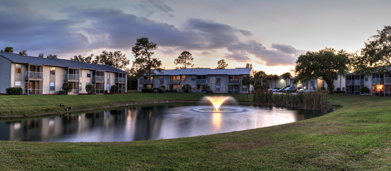 Banco che trascura un grande stagno con una fontana al tramonto fotografia stock libera da diritti