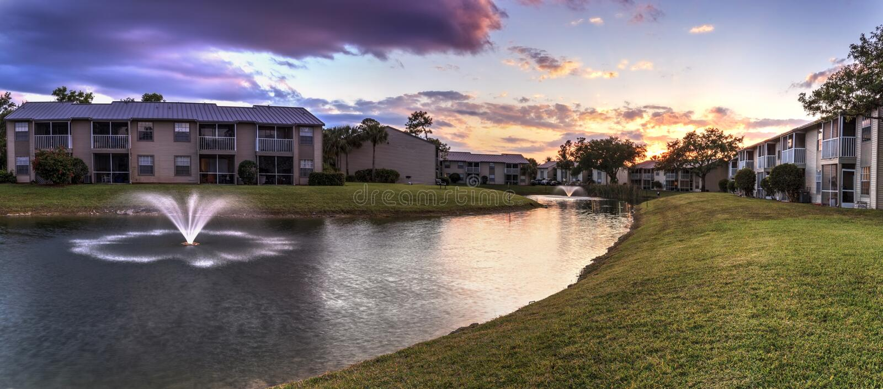 Banco che trascura un grande stagno con una fontana al tramonto immagine stock libera da diritti