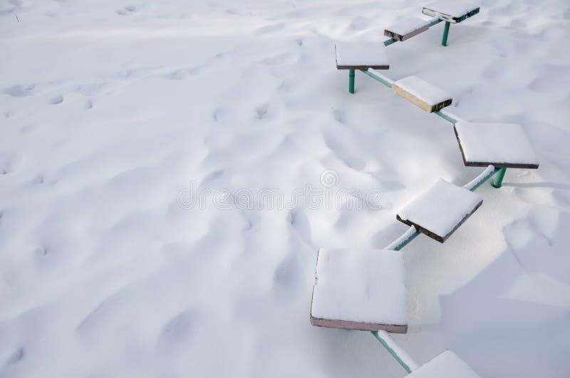 Banco coberto de neve com assentos coloridos no campo de jogos onde ninguém jogo fotografia de stock royalty free