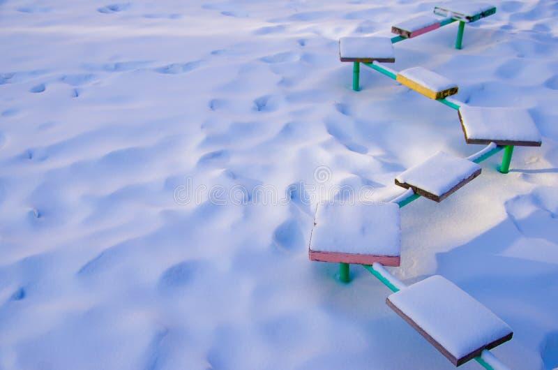 Banco coberto de neve com assentos coloridos no campo de jogos onde ninguém jogo fotos de stock