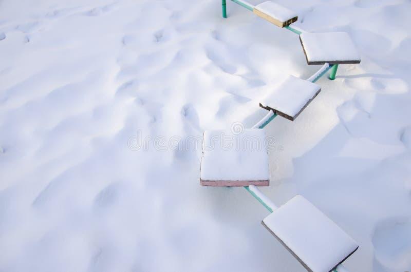 Banco coberto de neve com assentos coloridos no campo de jogos onde ninguém jogo imagens de stock royalty free