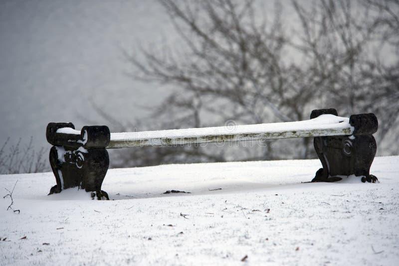 Banco coberto de neve do inverno em um parque fotos de stock royalty free