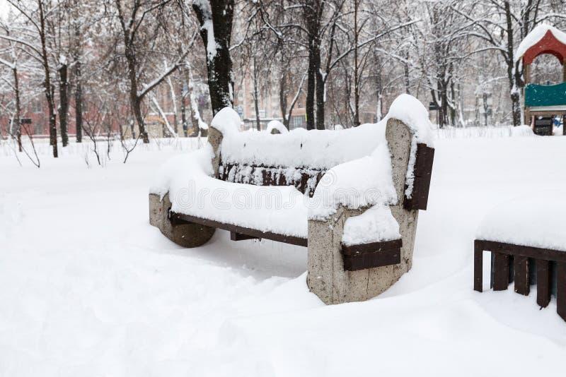 Banco coberto de neve entre snowbanks no parque da cidade imagens de stock