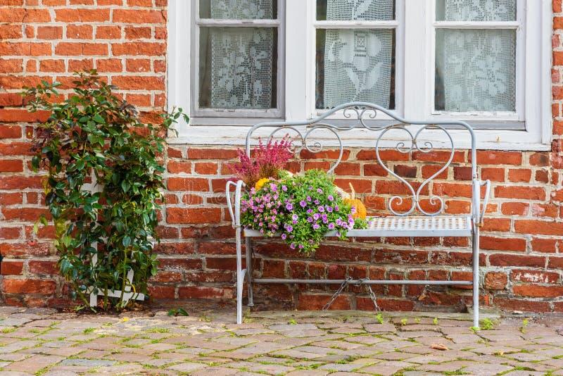 Banco con i fiori e le zucche alla vecchia casa con mattoni a vista Luneburg germany fotografia stock