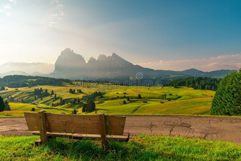 Banco con nadie en italiano las montañas de Dolomiti durante salida del sol Seiser Alm o ubicación de Alpe di Siusi, el Tyrol del imagenes de archivo