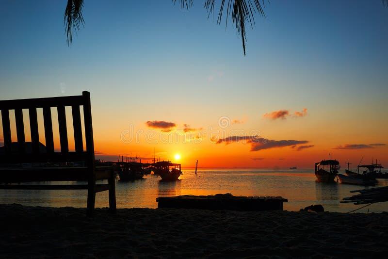 Banco con salida del sol hermosa en fondo en paisaje tropical del rong de la KOH de la playa con los barcos del longtail mientras fotos de archivo