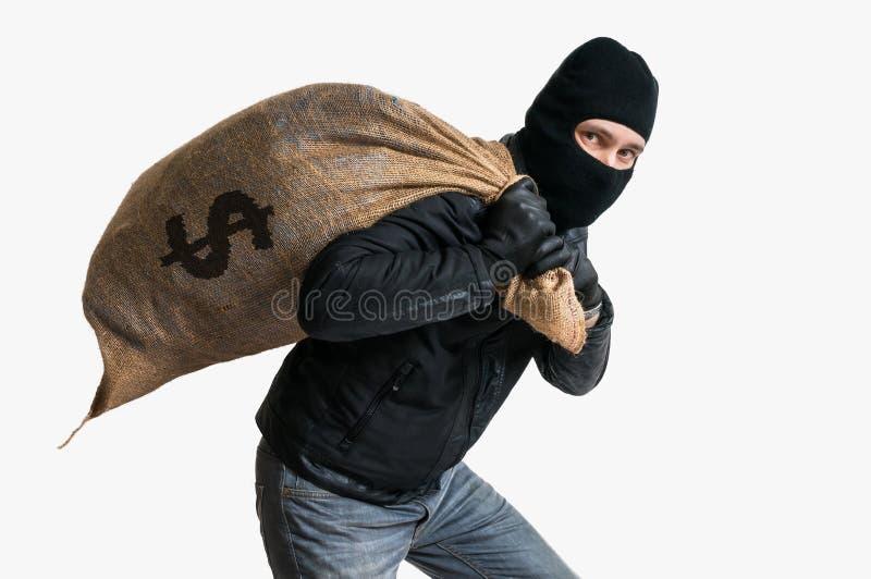 Banco con túnica del ladrón con el bolso lleno del dinero Aislado en el fondo blanco fotografía de archivo