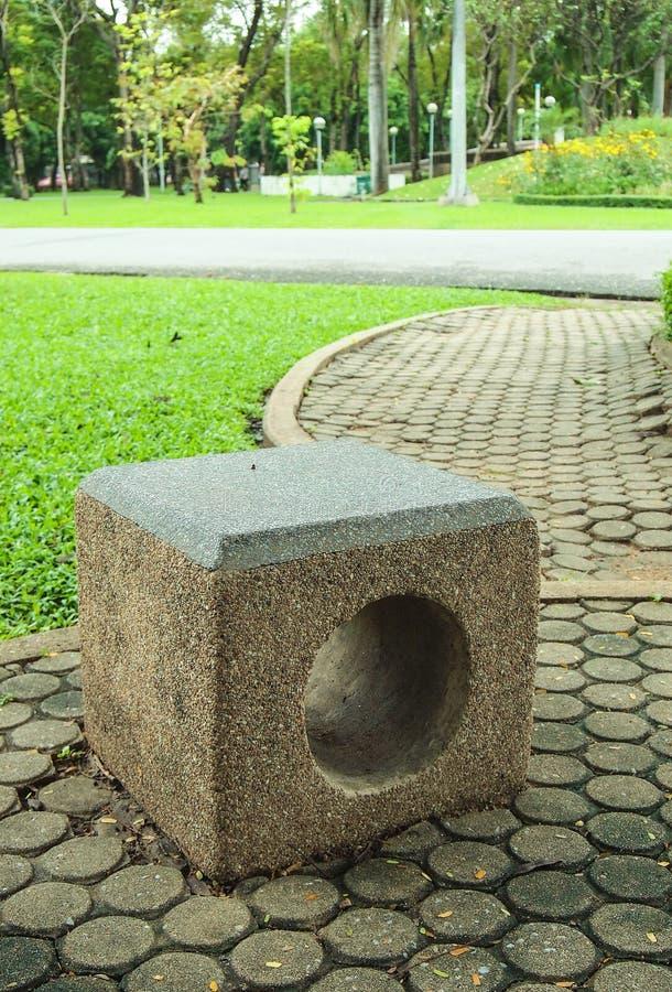 Banco concreto della scultura nel parco fotografia stock