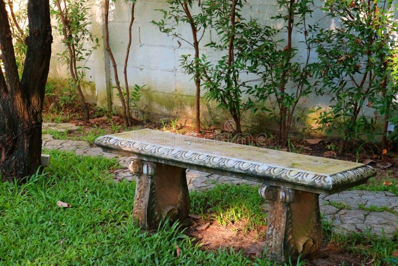 Banco d'annata della pietra di stile sul campo di erba verde di un parco pubblico fotografie stock