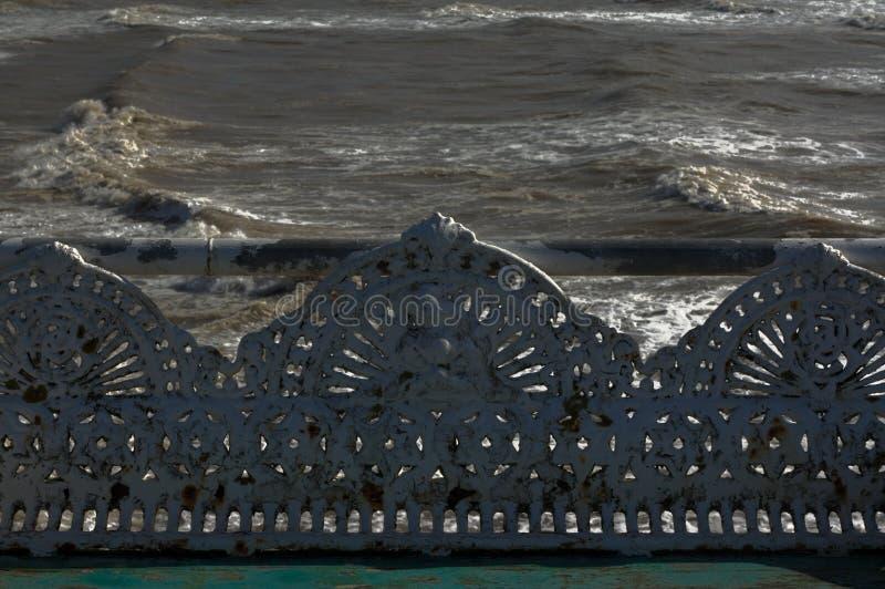 Banco de la antigüedad del arrabio en la playa fotos de archivo libres de regalías