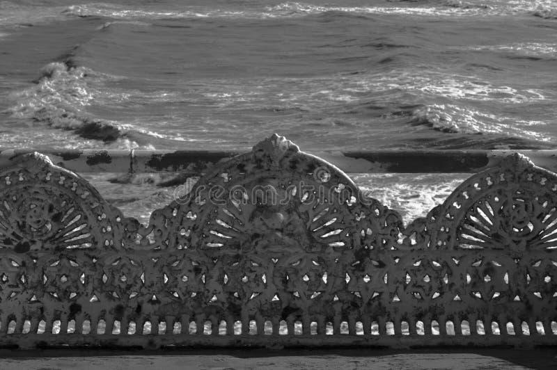 Banco de la antigüedad del arrabio en la playa imagenes de archivo