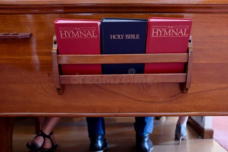 Banco de la iglesia con la biblia y los libros de himnos imagen de archivo libre de regalías