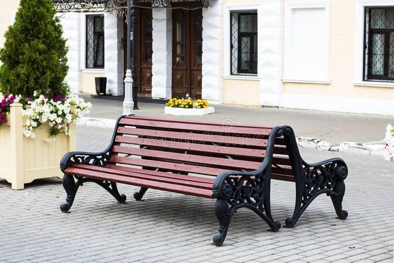 Banco de madeira de Brown em uma cidade ao lado do arbusto e das flores verdes, assento exterior do estilo do vintage Vida de Unb fotos de stock