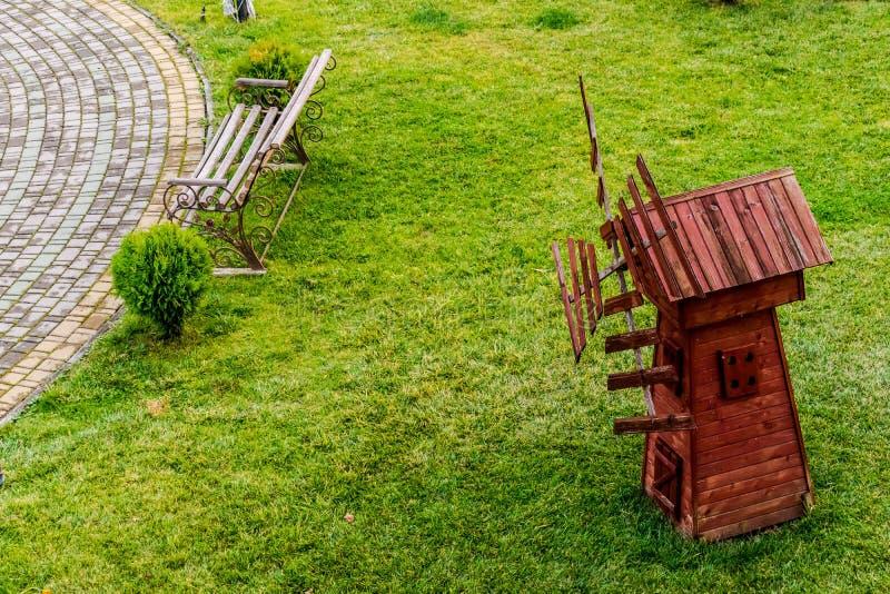 Banco de madeira e moinho de vento rústico imagens de stock royalty free