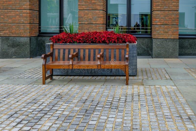 Banco de madeira lustrado na frente de um plantador do flowre com as plantas vermelhas e verdes foto de stock