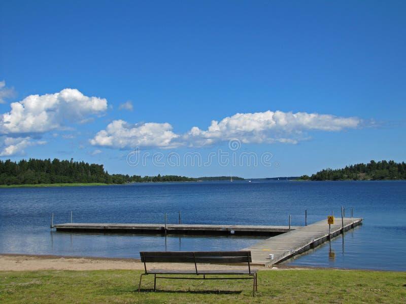 Banco de madeira na costa do lago Bia-Karen em Éstocolmo imagens de stock royalty free