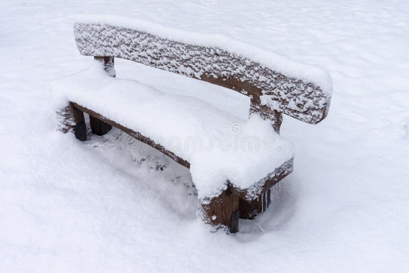 Banco de madeira rústico coberto de neve em um parque do inverno foto de stock royalty free