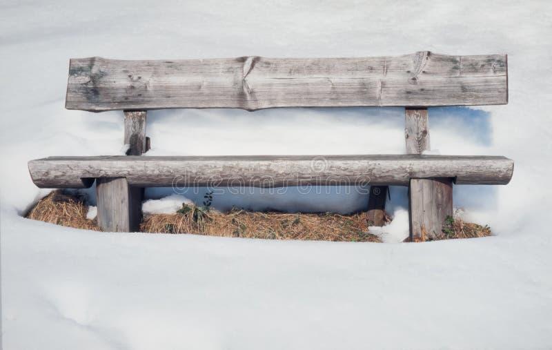 Banco de madeira rústico velho cercado por lotes da neve imagem de stock