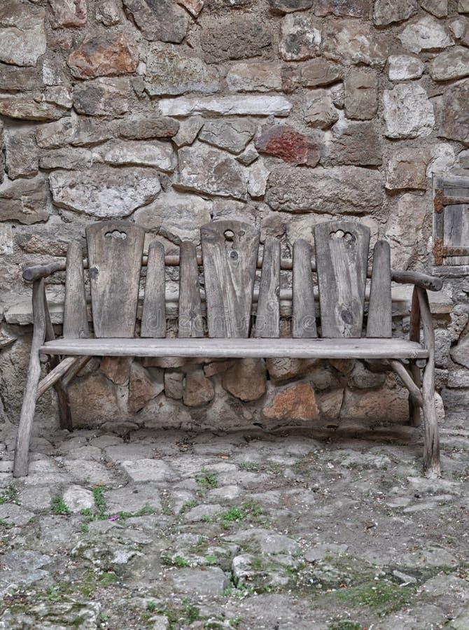 Banco de madeira velho na casa de pedra fotos de stock