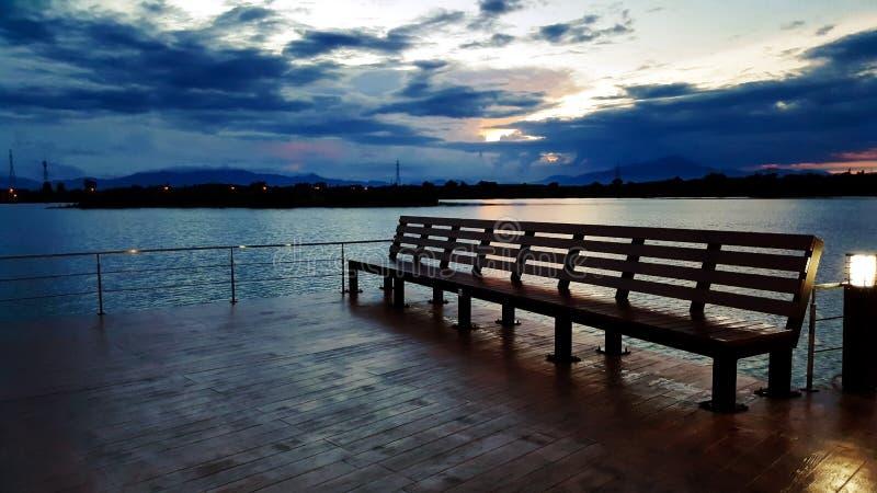 Banco de madera al aire libre con la vista del río en parque fotografía de archivo