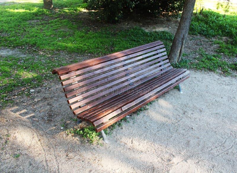 Banco de madera de Brown con los asientos en un lado en el parque imagen de archivo
