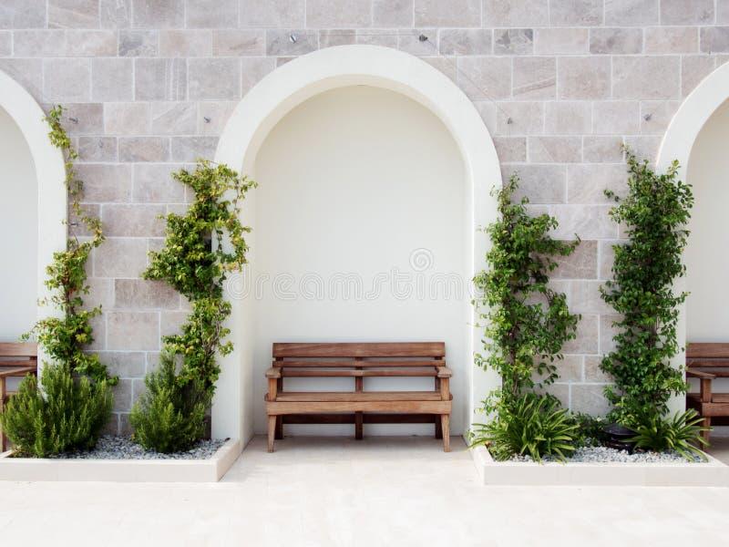 Banco de madera cerca de la pared de mármol blanca, espacio de la copia fotografía de archivo libre de regalías