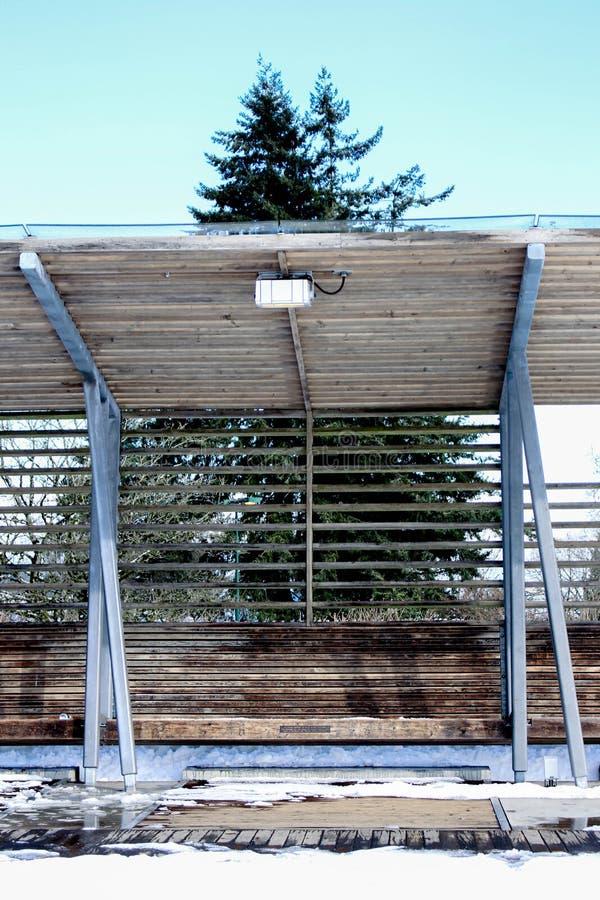 Banco de madera con nieve Cubierta de un parque fotografía de archivo libre de regalías